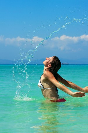 caucasian water drops: Young woman plays in water Stock Photo