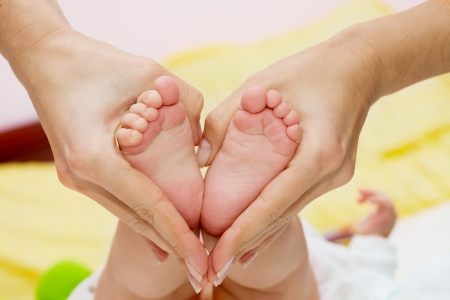 infant: Pies de beb� en manos de Mami
