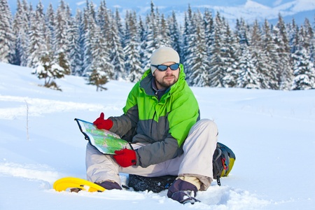 Hiker took a rest and is looking for the way on the map in snow forest photo