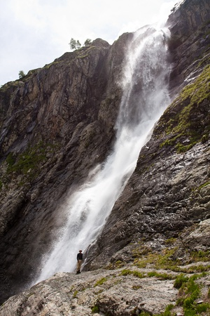Hiker in Caucasus mountains near huge waterfall  photo