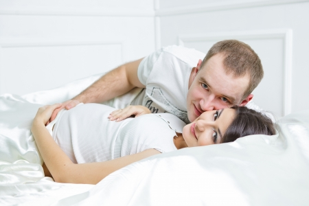 affinity: Happy pregnant family lies on the house bed.
