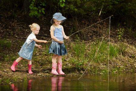 atrapar: Las ni�as son la pesca en el lago en el bosque