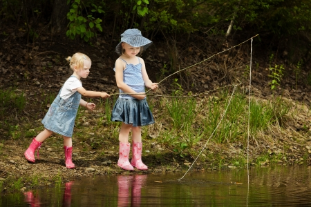 catch of fish: Little girls are fishing on lake in forest Stock Photo