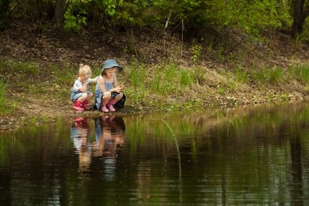 Little girls are fishing on lake in forest photo