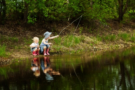 children pond: Little girls are fishing on lake in forest Stock Photo
