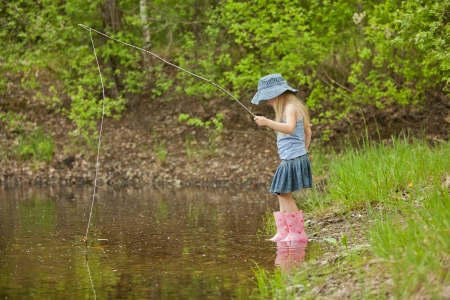 children pond: Little girl are fishing on lake in forest Stock Photo
