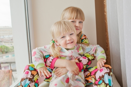 Two girls play at the windows-sill in pyjamas before sleep Stock Photo - 15050717