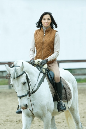 Woman jockey is riding the horse outdoor  photo