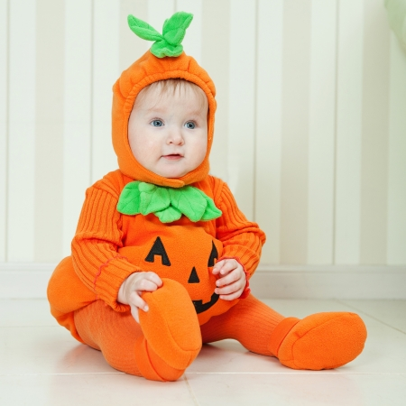 Baby in pumpkin suit on Halloween eve