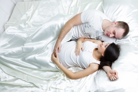 Happy pregnant family lies on the house bed. photo