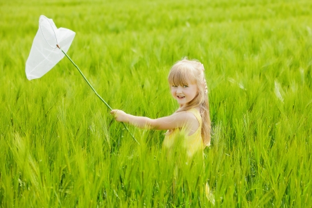 Girl with butterfly net having fun at field photo