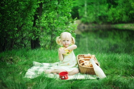 Girl have picnic at the lake with milk and buns photo
