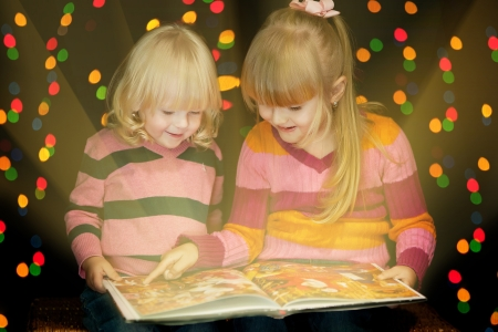 Two girls read book of tales on the Cristmas Eve  photo