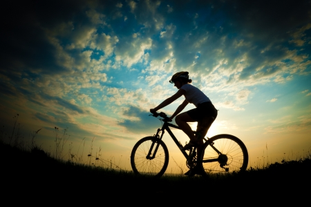 mountain bike: Biker-girl at the sunset on the meadow Stock Photo