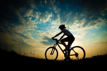 ciclista: Biker-girl en la puesta de sol en la pradera