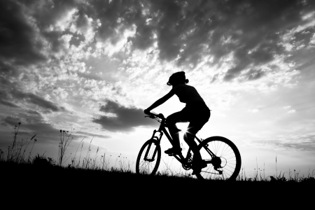 bicycle silhouette: Biker-girl at the sunset on the meadow Stock Photo