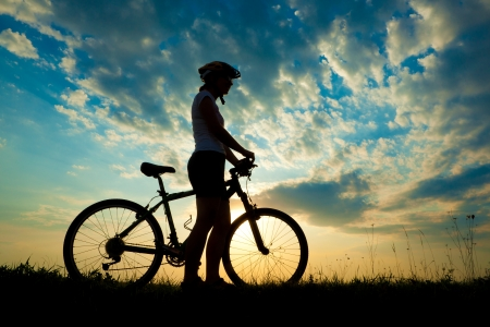 Biker-girl at the sunset on the meadow 版權商用圖片