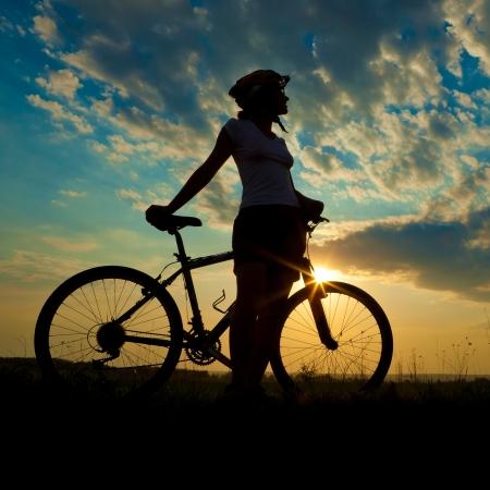 biker girl: Biker-girl at the sunset on the meadow Stock Photo