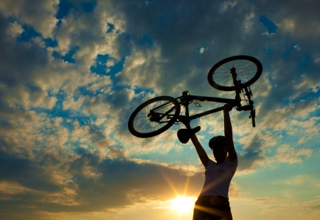 Biker holds bike high up in the sky