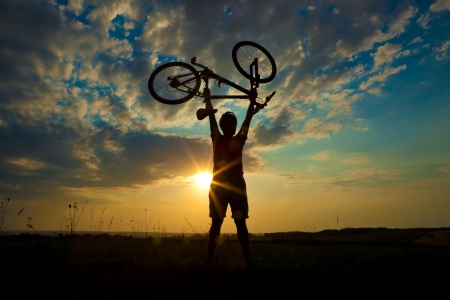 ciclista: Motociclista sostiene moto alto en el cielo