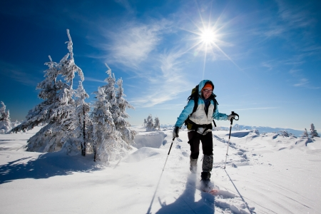 Hiker in winter mountains snowshoeing photo