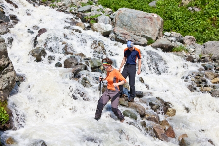 Hiker is crossing mountain river in Svaneti Georgia photo