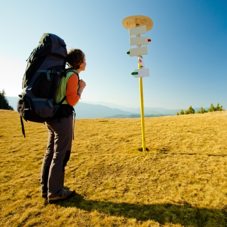 rambling: Hiker women is looking at arrow signs in mountains
