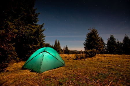 bonfire night: Tent illuminated with light in night forest