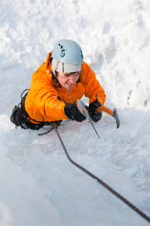 Man climbing frozen waterfall photo