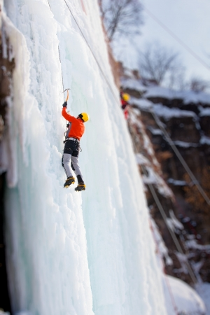ice climbing: Man climbing frozen waterfall Stock Photo