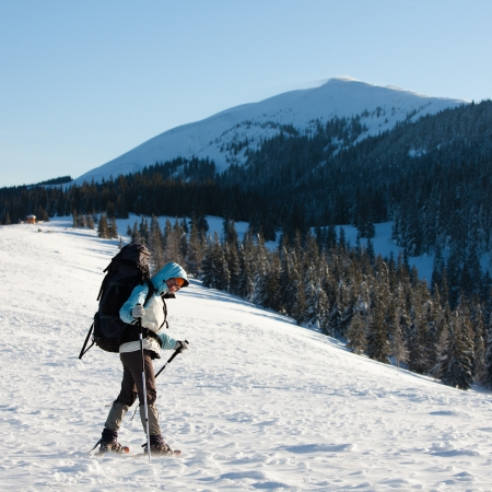Hiker in winter mountains photo