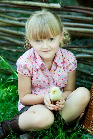 Girl plays with chicken photo