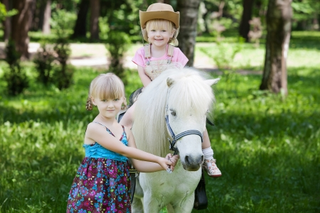 ponies: Girls take a walk with pony Stock Photo