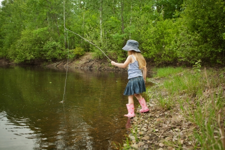 Little girl are fishing on lake in forest photo