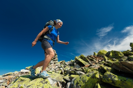 Hiker jumps over stones in Carpathian mountains