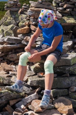 Athlet looking girl fixes bandage on knees outdoor photo
