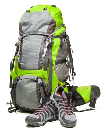 camping equipment: Hiking shoes and packed backpack on white background