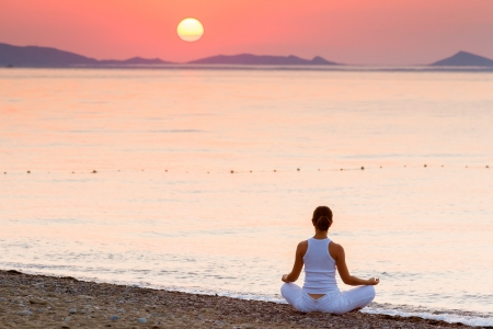 Woman is doing morning excercises at the sea during sunrise photo