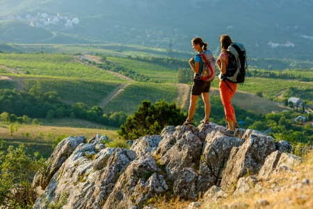 freedom leisure activity: Two women is trekking in the Crimea mountains with backpacks