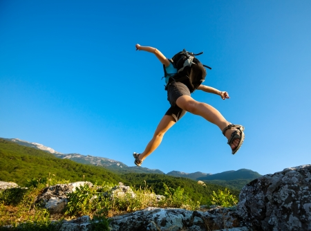 adventure sports: Hiker jumps over the rock Stock Photo