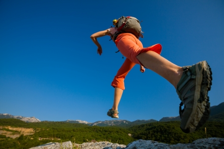 climbing mountain: Hiker jumps over the rock Stock Photo