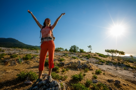 Happy woman at the sunrise in mountains photo