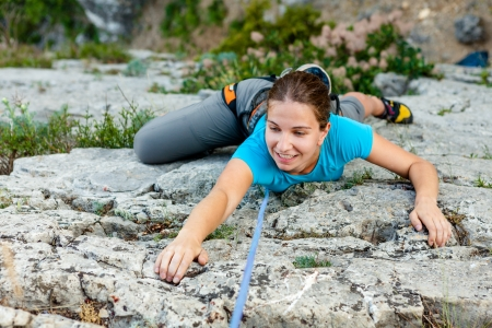 daring: Woman practices in climbing at the rock in the Crimea mountains