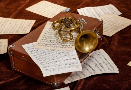 music score: Vintage trumpet is lying between paper sheets with notes