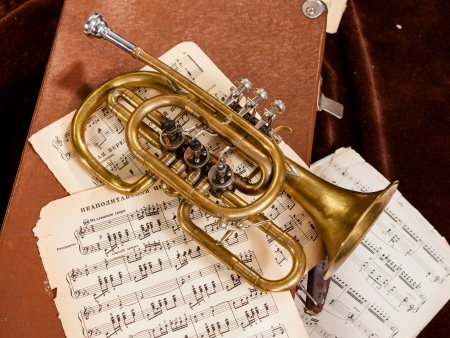 Vintage trumpet is lying between paper sheets with notes photo