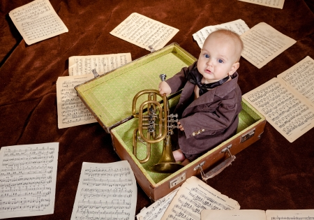 Caucasian baby boy plays with trumpet between sheets with musical notes against brown background photo