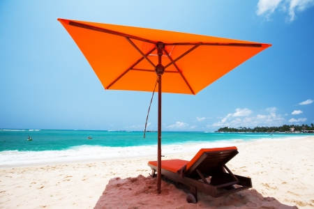 indian ocean: Tropical beach at Indian Ocean. Red umbrella and lounge at the sea. Stock Photo