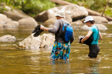 Trekkers are fording river in Singharaja Forest in Sri Lanka