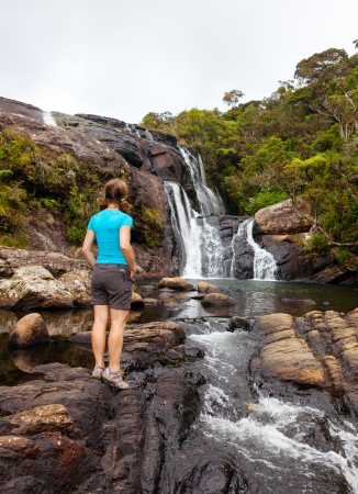 Trekker looks at wild waterfall in Horton Plains National Park, Sri Lanka photo