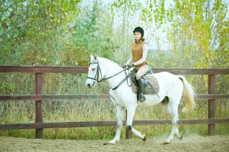 Femme jockey monte le cheval en plein air photo